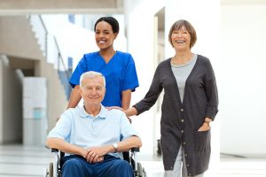 A nurse pushing a smiling man in a wheelchair next to his wife