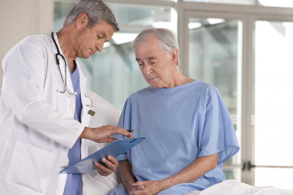 Doctor explaining a medical chart to an elderly patient