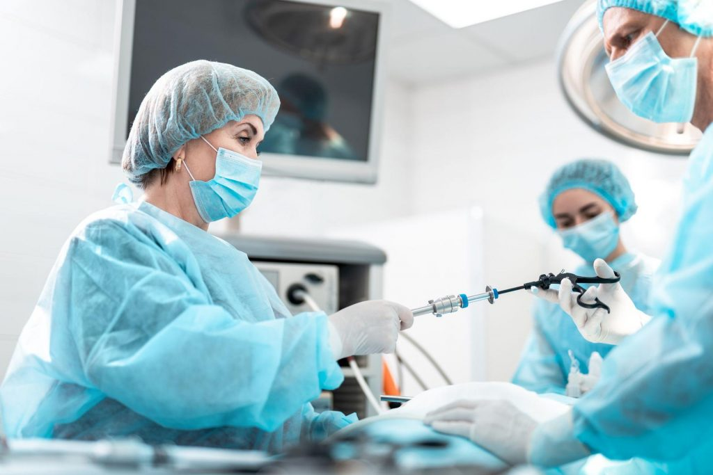 Doctors using a large machine during surgery
