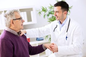 A doctor shaking the hand of an elderly patient