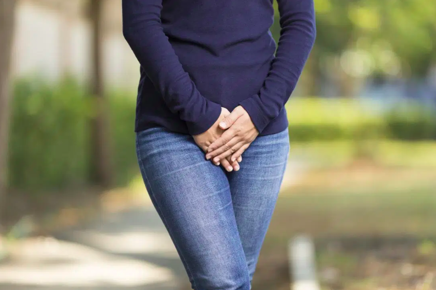 A lady holding her hands over her groin